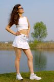Beautiful young girl in white mini skirt on the beach. Happy young beautiful woman in white posing at the beach summer morning royalty free stock photos