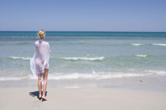 Beautiful young girl in white walking on the beach Royalty Free Stock Photography