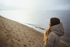 Beautiful young girl in winter jacket relaxing with closed eyes at winter sunset by the river. Stock Photo