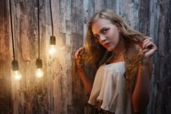 Beautiful woman photo. Beautiful young girl woman lady standing near light bulbs, she had a brilliant idea. Illumination of consciousness smart idea. Dreaming Royalty Free Stock Images