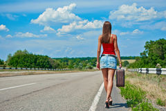 Beautiful young girl or woman in mini with suitcase hitchhiking along a road Stock Images