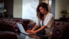 Beautiful young girl woman office employee manager sits at a table with a laptop. Luxury interior . Concentrated female royalty free stock images