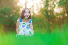 A beautiful young girl in the woods smiling. A beautiful young happy girl smiles looking off into the distance Stock Photo