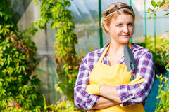 Beautiful young girl working in a greenhouse. Gardener Royalty Free Stock Photography