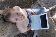 Beautiful young girl working with laptop in tree Stock Photo