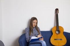 A beautiful young girl writes songs. A beautiful young girl writes songs in a notebook and sits next to the guitar royalty free stock photo