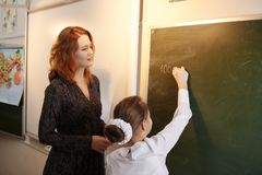 Beautiful young girl writing on blackboard in classroom. Beautiful young teacher writing on blackboard in classroom Stock Photos