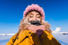 Beautiful young girl in a yellow down jacket and pink knitted cap with red hair   in a frost in the background of the camp Barneo Royalty Free Stock Photography