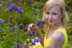 Girl in purple flowers outdoors in summer Stock Photos