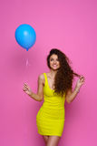 Beautiful and young girl in a yellow dress holding a blue balloon and smiling on a pink background Stock Photography