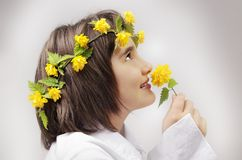 Beautiful young girl with yellow flowers Stock Image