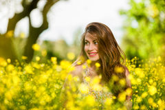 Beautiful young girl among yellow flowers Stock Images