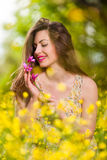 Beautiful young girl among yellow flowers Stock Photo