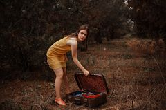Beautiful young girl in a yellow vintage dress standing in the rain by an open vintage suitcase with scattered clothes.  stock photo