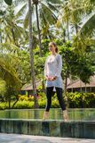 Beautiful young girl in yoga wear is practicing yoga, meditation, standing on the swimming pool in resort in Indonesia