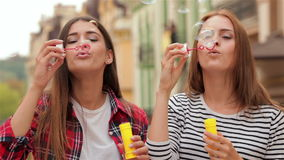 Beautiful young girls blowing bubble outdoor. Beautiful young woman blowing bubble outdoor happy lifestyle. Gorgeous young girl blowing soap bubbles on city stock video