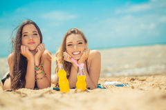 Beautiful young girls drinking water from boutle on the beach Stock Photography