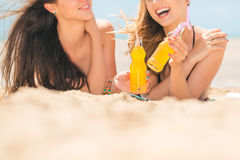 Beautiful young girls drinking water from boutle on the beach Royalty Free Stock Images