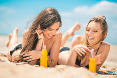 Beautiful young girls drinking water from boutle on the beach Royalty Free Stock Photo