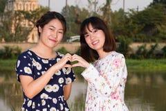 Beautiful Young girls fashion portrait make heart shape Royalty Free Stock Image