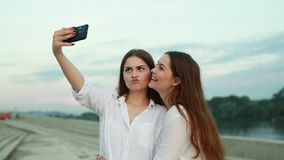 Beautiful young girls. Beautiful young girl twins in the summer at sunset are photographed on the phone and crooked stock footage