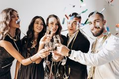 Beautiful young girls and guys dressed in stylish elegant clothes smile together and clink glasses with champagne on a royalty free stock photos
