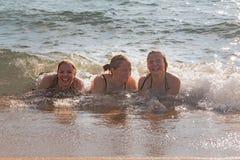 Waves Splash Girls Laying on the Sand Stock Photo