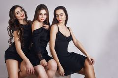 Beautiful young girls with make-up, red lips, pretty face . Womans on white background. Cheerful young womans wearing black dress, royalty free stock photos