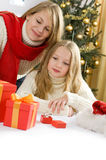 Beautiful young girls opening their presents. Fir christmas tree with golden glass balls in background Royalty Free Stock Images
