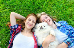 Beautiful young girls playing with her dog Royalty Free Stock Photos