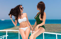 Beautiful young girls in swimsuit standing on the yacht at a sun royalty free stock photos
