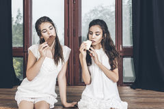 Beautiful young girls in white dresses sitting with chocolate on stock photo