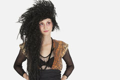 Beautiful young Goth woman with teased hair looking away over gray background Stock Image