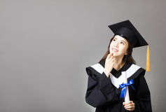 Beautiful young  graduate holding diploma and thinking Stock Photo