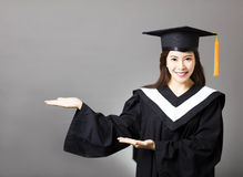 Beautiful young  graduate with showing gesture Royalty Free Stock Images
