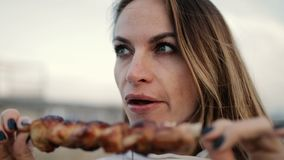 Beautiful woman biting huge pieces of meat eating with hands angry inappropriate in close up view. Beautiful young greedy woman biting huge pieces of meat eating stock video