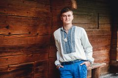 Beautiful young guy in an embroidered shirt on the background of a wooden house royalty free stock images