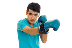 Beautiful young guy practicing boxing in blue gloves isolated on white background Royalty Free Stock Images