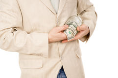 Beautiful a young guy trying to extract money from a glass conta Royalty Free Stock Image