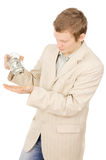 Beautiful a young guy trying to extract money from a glass conta Stock Photography