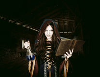 Free Beautiful Young Halloween Witch Holding Magical Book And Poison Stock Photo - 59445990