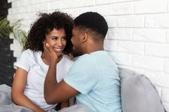 Beautiful young happy african-american couple in bed stock images