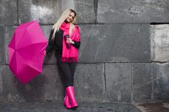Beautiful young and happy blond woman with colorful umbrella on the street. The concept of positivity and optimism. Girl in a bright pink scarf, rubber boots Royalty Free Stock Photography