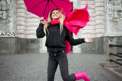 Beautiful young and happy blond woman with colorful umbrella on the street. The concept of positivity and optimism Royalty Free Stock Photo