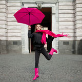 Beautiful young and happy blond woman with colorful umbrella on the street. The concept of positivity and optimism. Girl in a bright pink scarf, rubber boots Stock Photo