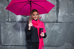 Beautiful young and happy blond woman with colorful umbrella on the street. The concept of positivity and optimism Royalty Free Stock Image