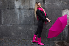 Beautiful young and happy blond woman with colorful umbrella on the street. The concept of positivity and optimism. Girl in a bright pink scarf, rubber boots royalty free stock photos