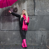 Beautiful young and happy blond woman with colorful umbrella on the street. The concept of positivity and optimism Royalty Free Stock Images
