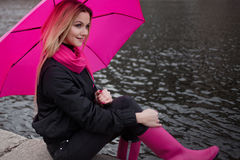 Beautiful young and happy blond woman with colorful umbrella on the street. The concept of positivity and optimism Royalty Free Stock Photography