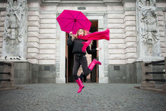 Beautiful young and happy blond woman with colorful umbrella on the street. The concept of positivity and optimism. Girl in a bright pink scarf, rubber boots Stock Photography